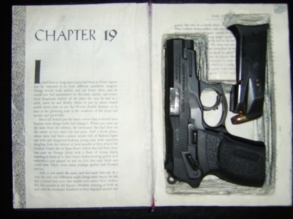 Secret hollow book compartment holding a pistol and magazine