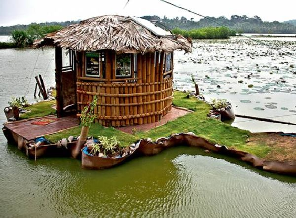 Small floating Island with green cottage rests on 5,000 used plastic