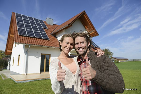 Portrait of couple giving thumbs up outside new home