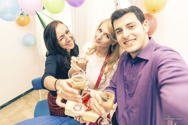 Group of friends celebrating birthday - Young man holding camera and taking a picture with camera while at his girlfriend's party - Young attractive people at party toasting champagne glasses and having fun