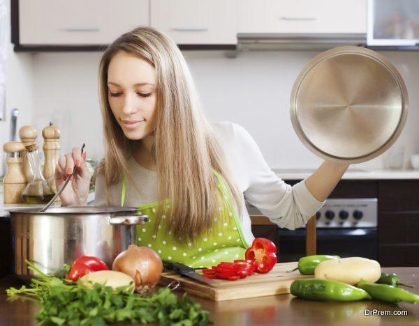 Ordinary blonde woman with ladle testing soup from pan in  kitchen