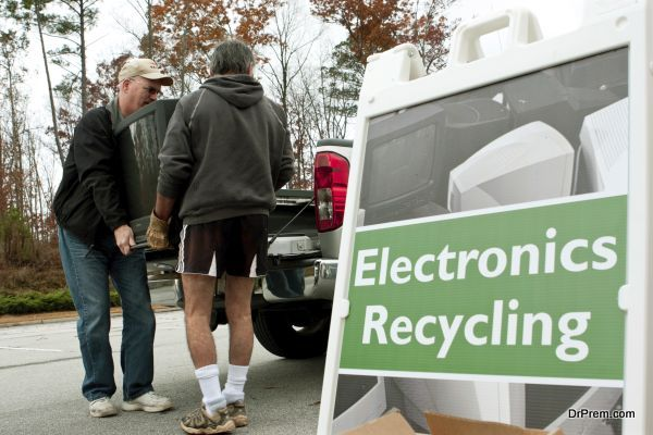 """Lawrenceville, GA, USA - November 23, 2013:  Two men carry a discarded television set past an """"Electronics Recycling"""" sign at Gwinnett County's America Recycles Day event."""