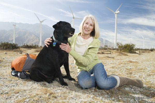 Portrait of a beautiful senior woman sitting with pet dog during vacation at wind farm