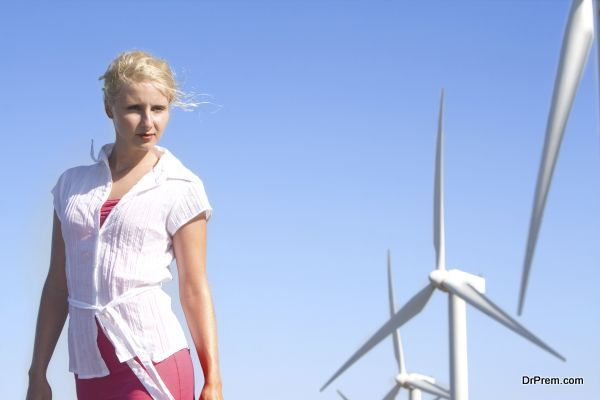 young woman dreams about the future on a wind farm beneath eolic generator