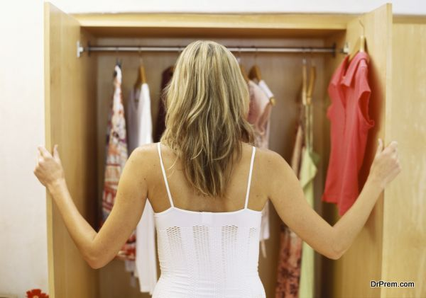 Rear view of a young woman looking into a  wardrobe