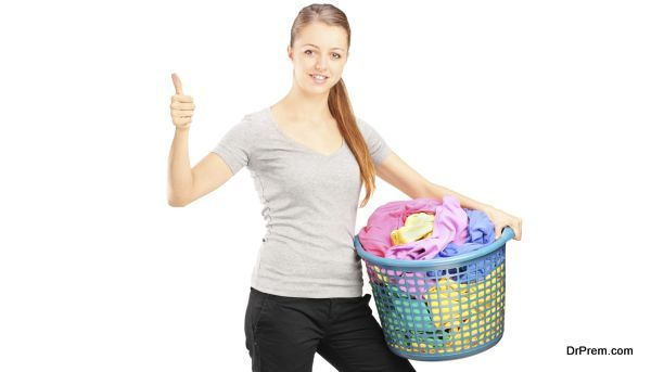 Young woman with basket full of clothes giving thumb up
