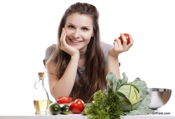 Young Woman Cooking in the kitchen. Healthy Food - Vegetable Salad. Diet. Dieting Concept. Healthy Lifestyle. Cooking At Home.