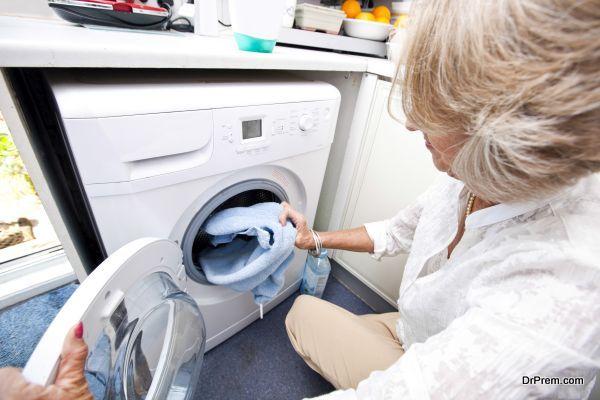 Senior woman loading towel in washing machine at home