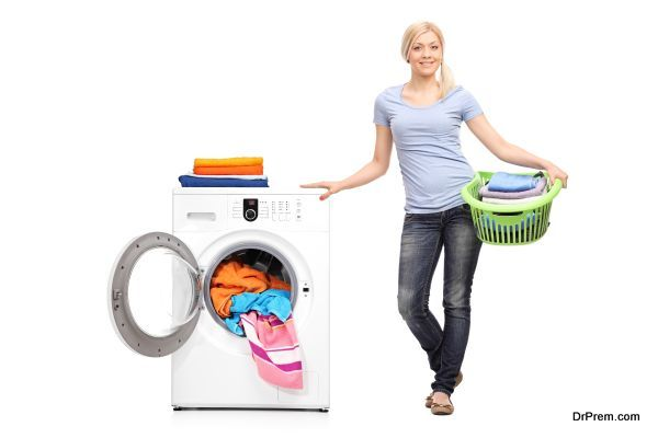 Woman holding laundry basket by a washing machine