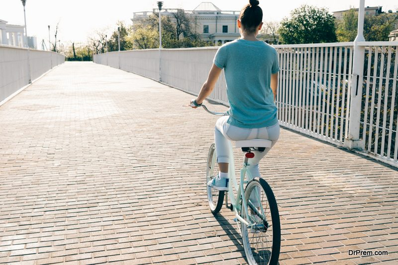 Slim girl in jeans and a T-shirt on a blue bike